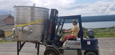Winemaker Vinny Aliperti driving a wine tank on a forklift.