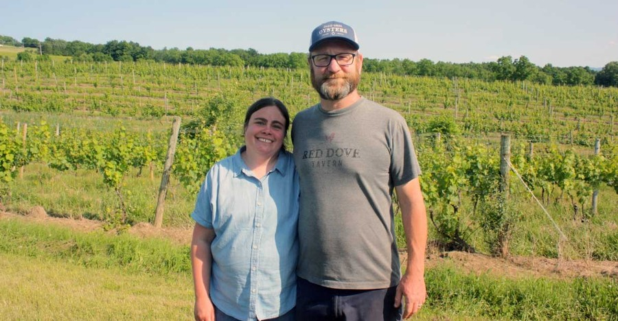 Owners of Red Dove Tavern standing in a vineyard.