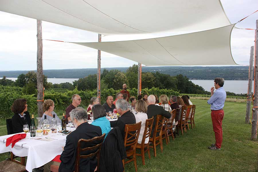 View of Seneca Lake from the vineyard set up for The Vineyard Table event.